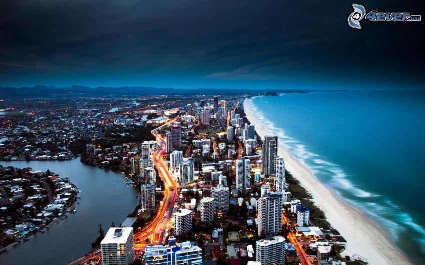 Gold Coast, sandstrand, hav, skyskrapor, kvällsstad