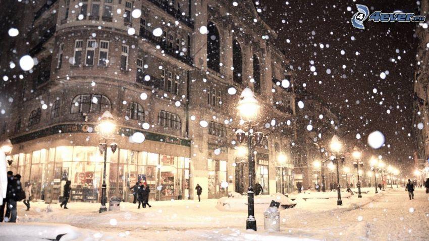 kvällsstad, snöig gata, gatlyktor, snöfall