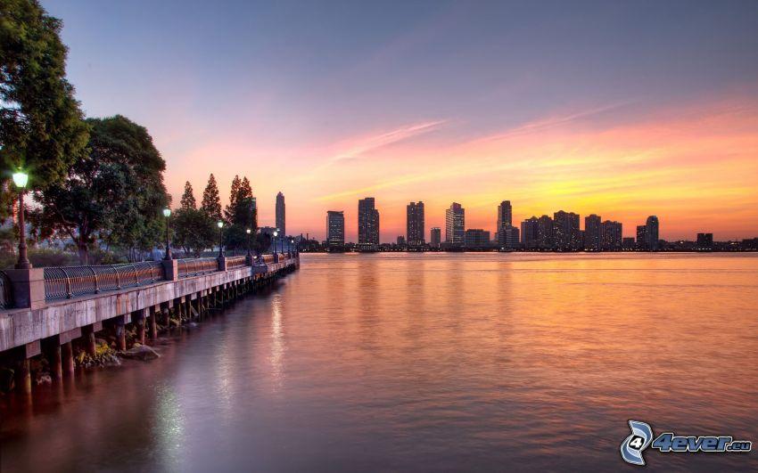 New York, solnedgång över stad, skyskrapor, kust