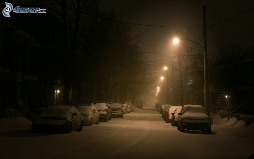 snöig gata, gatlyktor, bilar
