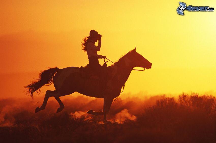 kvinna till häst, orange solnedgång