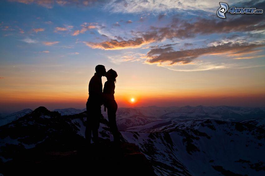 silhuett av ett par, solnedgång över berg, kyss