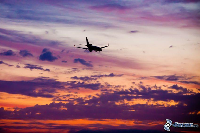 silhuett av flygplan, lila himmel, moln