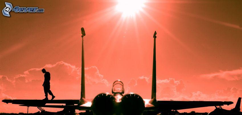 silhuett av jetplan, silhuett av man, sol