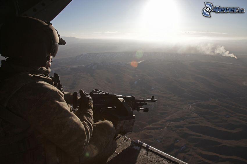 soldat med en pistol, bergskedja, solnedgång