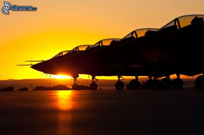 silhuetter av jetplan, solnedgång