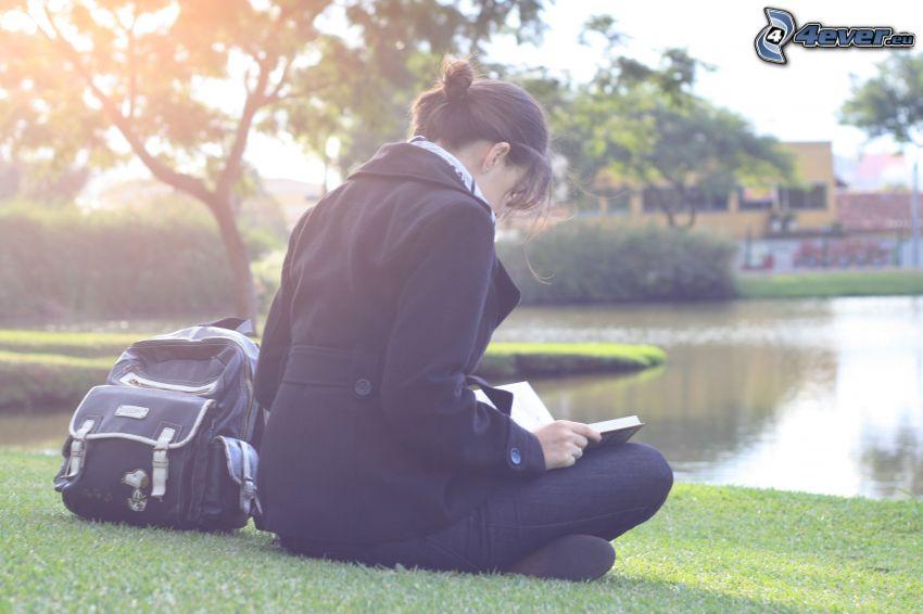 flicka med bok, sjö, park vid solnedgången
