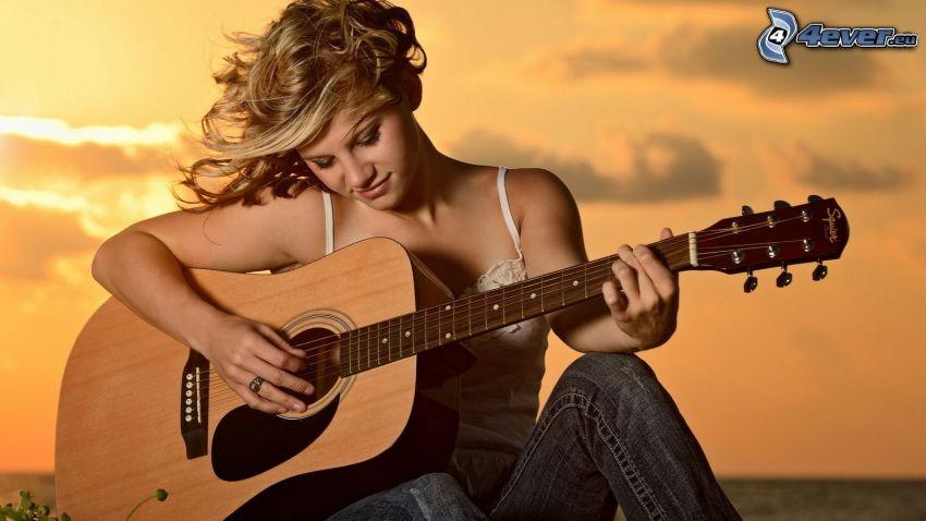 flicka med gitarr, orange solnedgång
