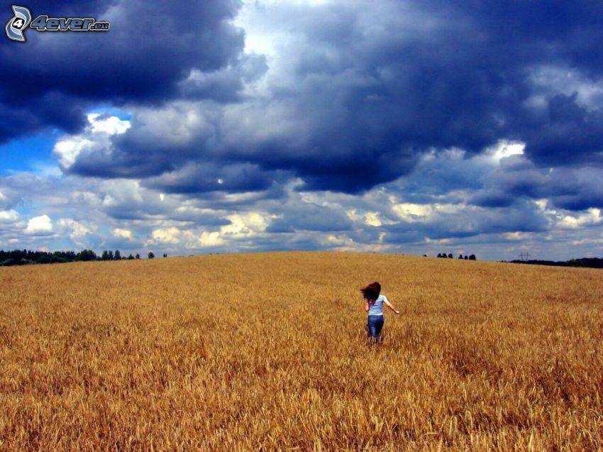 flicka på fält, mörka moln
