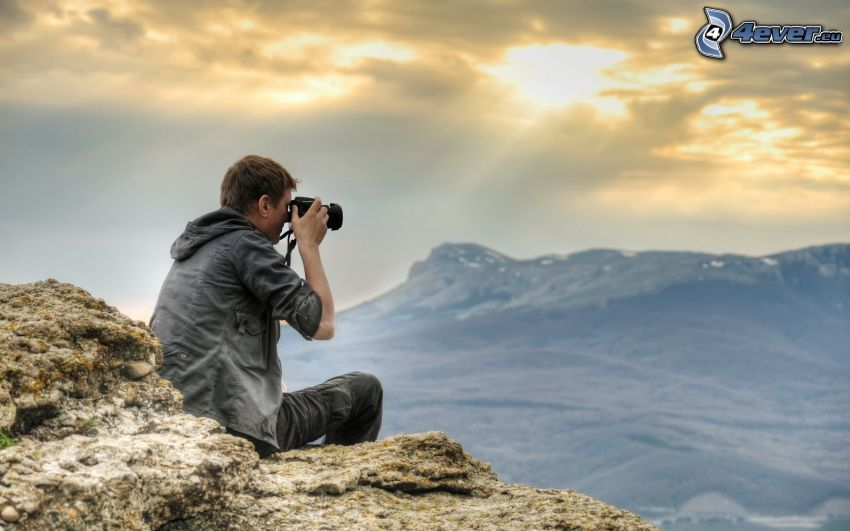 kille med kamera, berg, solstrålar