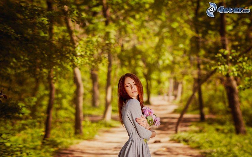 brunett, rosa blommor, skogsväg