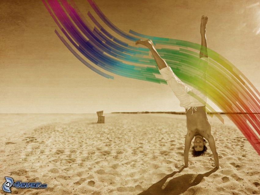 kille på strand, handstående, regnbågsfärger