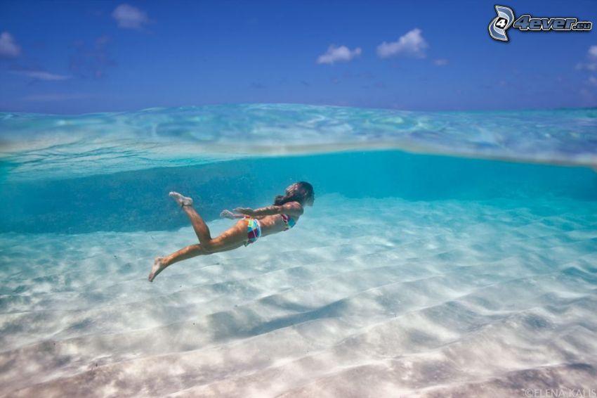 simmande under vatten, azurblå hav, sand