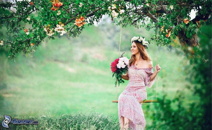 kvinna på gunga, bukett, blommande träd