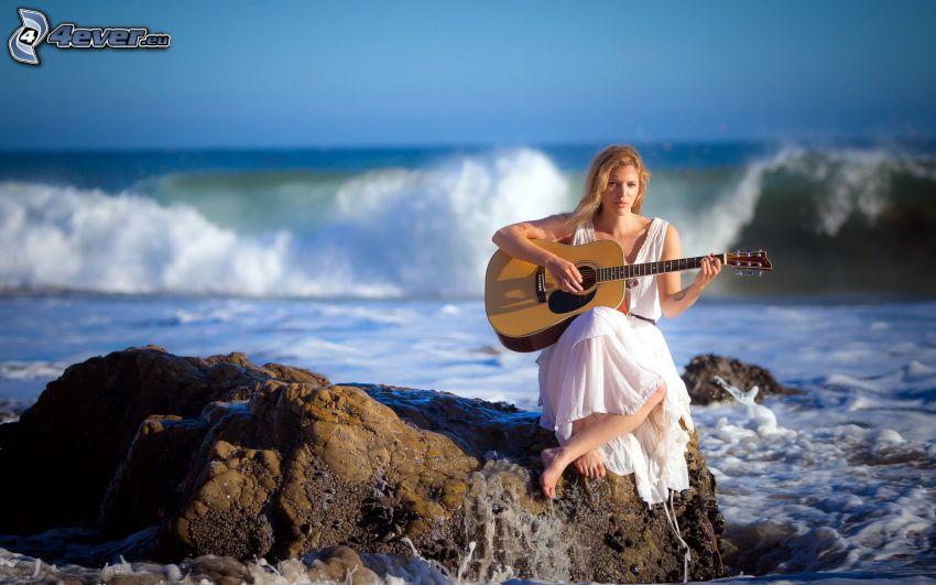 flicka med gitarr, klippstrand, våg