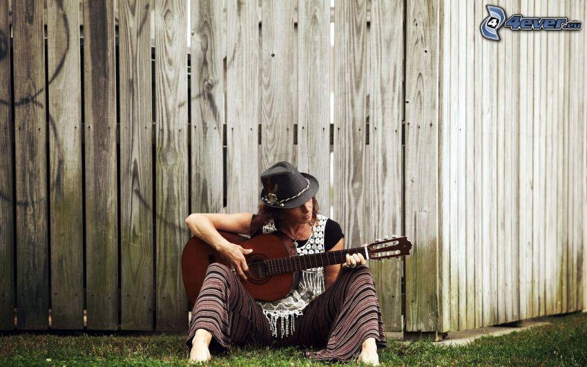 flicka med gitarr, trästaket