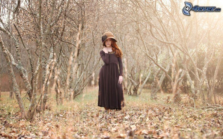 rödårig flicka, torra löv, kalt träd