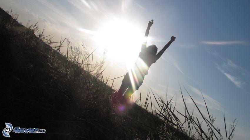 silhuett av kvinna, glädje, solnedgång över äng