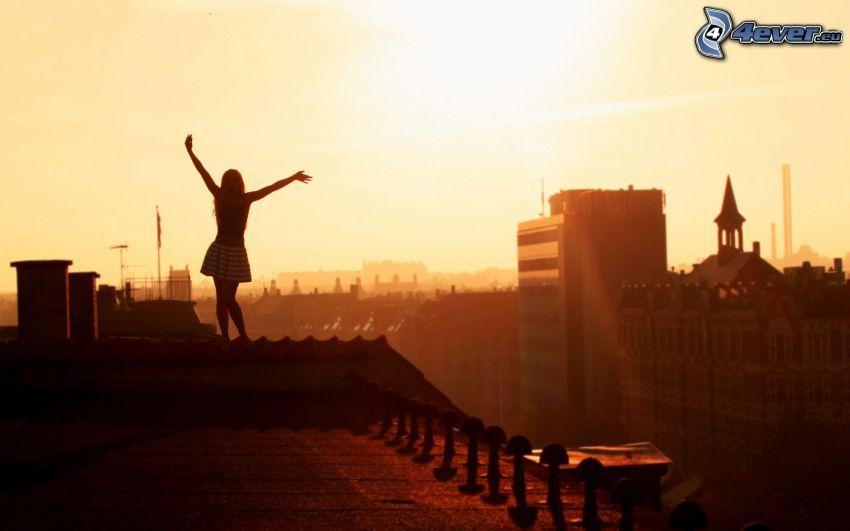 silhuett av kvinna, solnedgång i staden