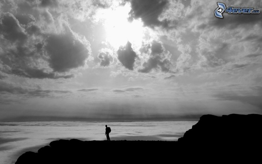 silhuett av man, hav, solstrålar bakom moln, svart och vitt