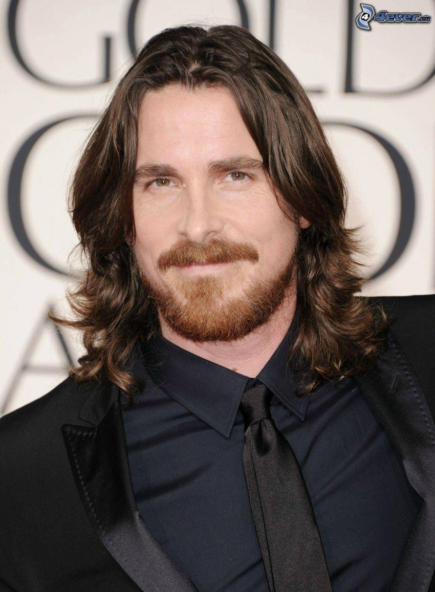 Christian Bale, man i kostym, långt hår, mustasch