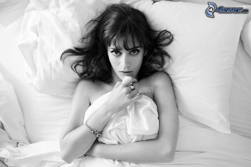 Lizzy Caplan, kvinna på säng, svartvitt foto