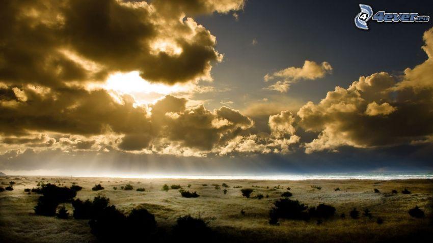äng, sol bakom molnen, solstrålar