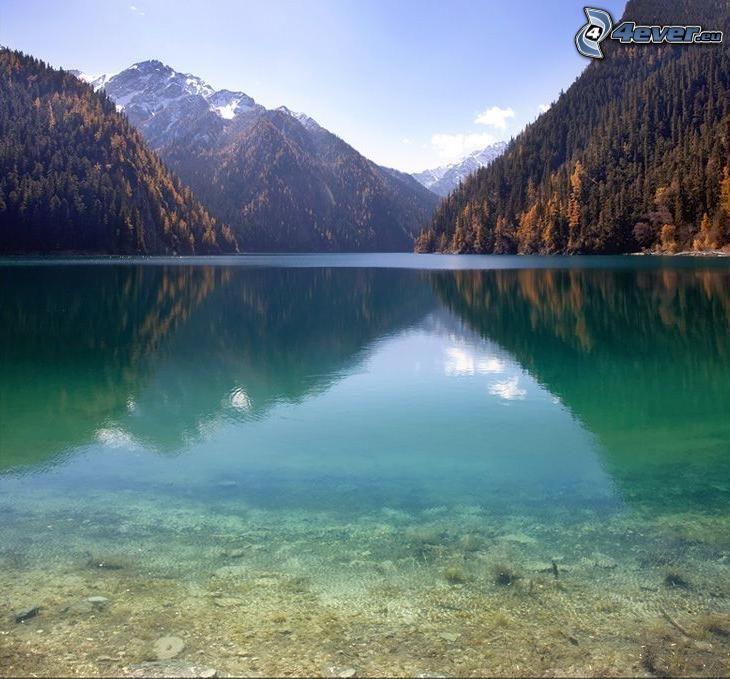 azurblå sjö, snöiga berg ovanför sjö, barrskog, gula träd