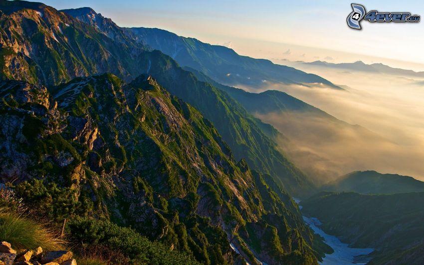 Alperna, klippiga berg, ovanför molnen