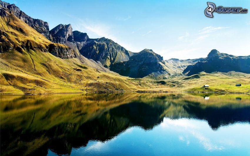Alperna, klippiga berg, tjärn, spegling