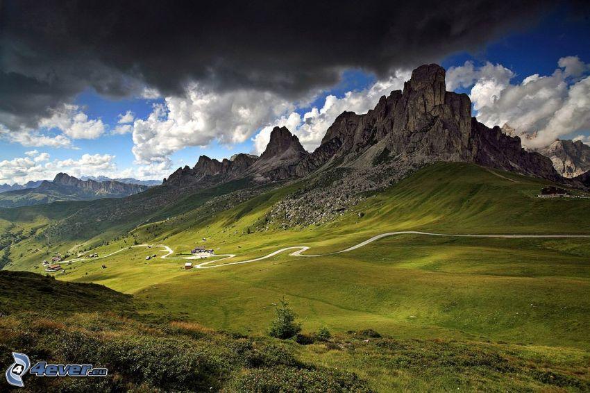 Dolomiterna, klippigt berg, mörka moln, väg