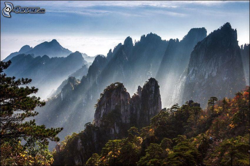 Huangshan, klippiga berg, solstrålar