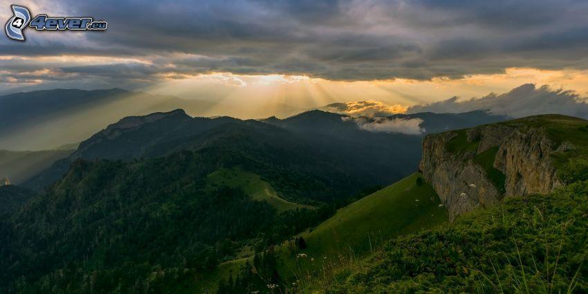 klippiga berg, grönska, utsikt över landskap, solstrålar bakom moln