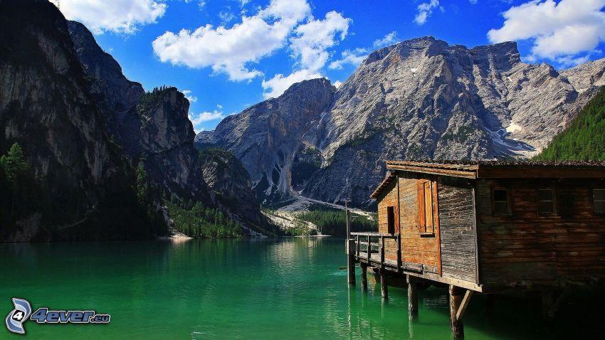 klippiga berg, hus på vatten, sjö