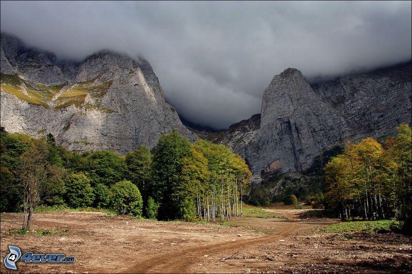 klippiga berg, lövträd, moln