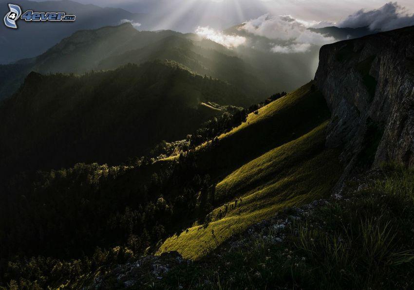klippiga berg, skog, solstrålar