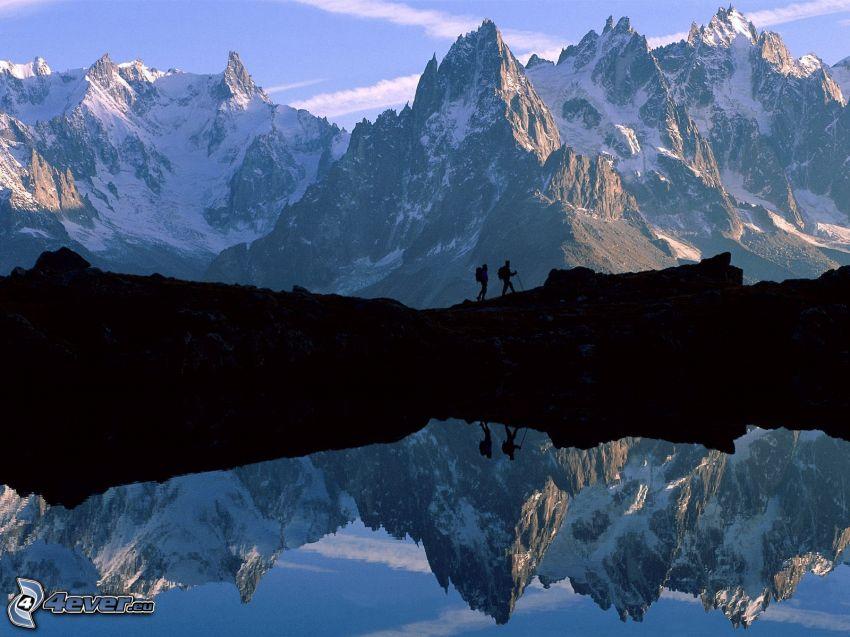 klippiga berg, turister, silhuetter av människor, tjärn, spegling