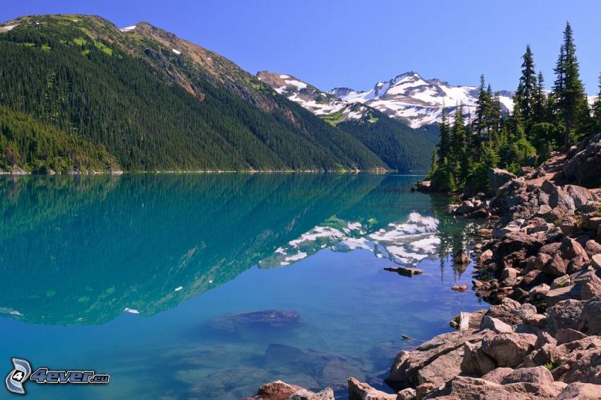 Moraine Lake, Banff National Park, sjö, stenar, snöiga kullar, barrträd