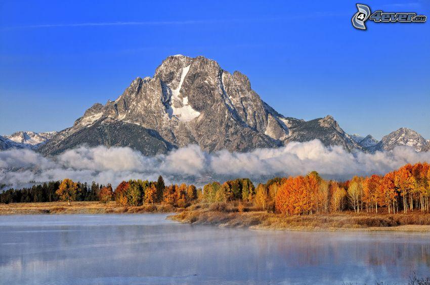sjö, klippigt berg, moln, gula träd