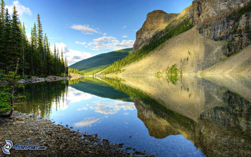 sjö i skogen, klippigt berg, barrskog, lugn vattenyta, spegling
