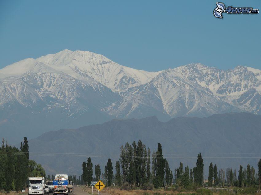 snöig bergskedja, lastbilar, väg