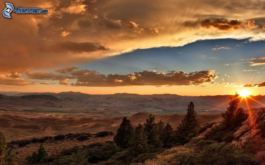 solnedgång bakom bergen, barrträd, moln