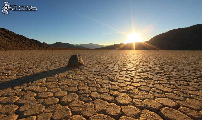 Death Valley, solnedgång över kulle, torr jord, sten