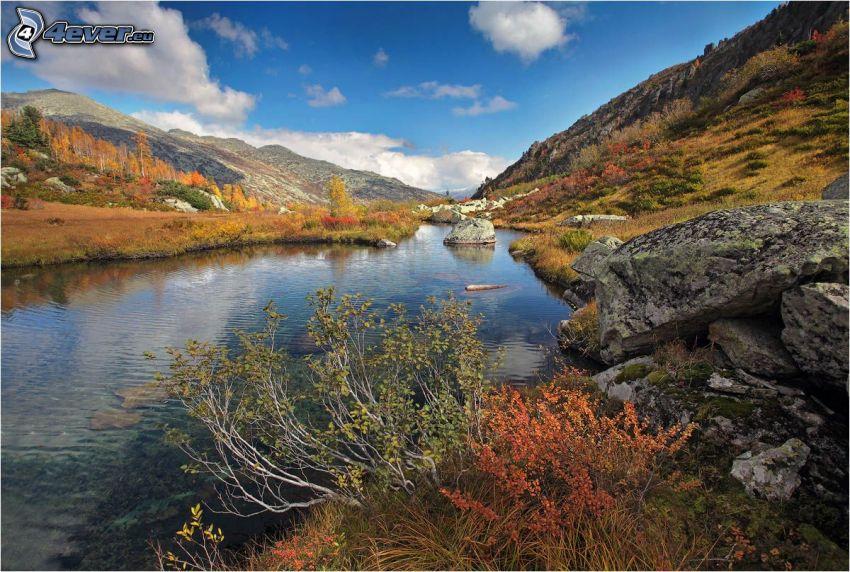 flod, klippor, kullar, färgglada höstträd
