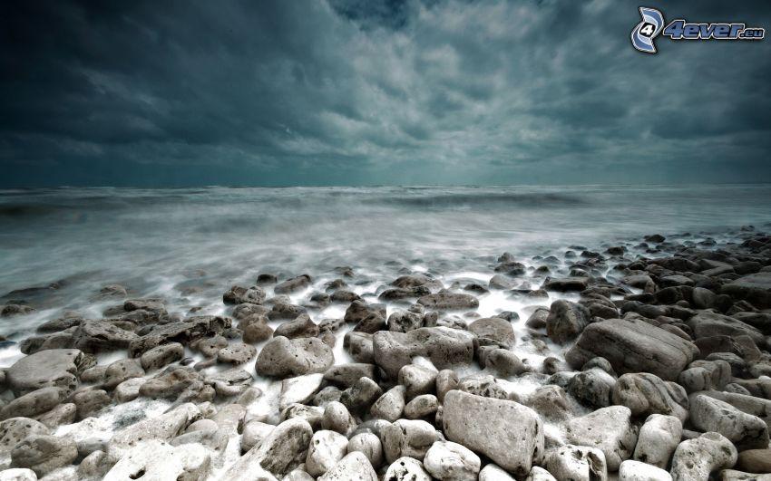 hav, stenig strand, mörk himmel