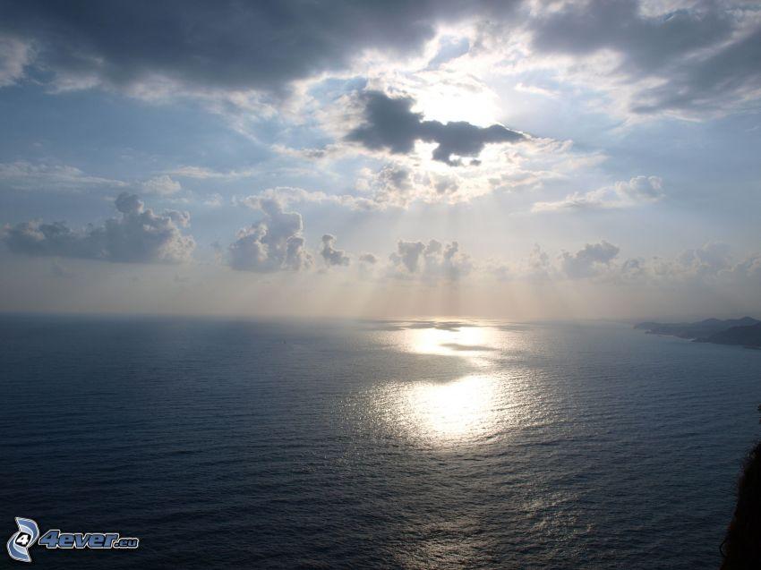 havsutsikt, solstrålar, sol bakom molnen