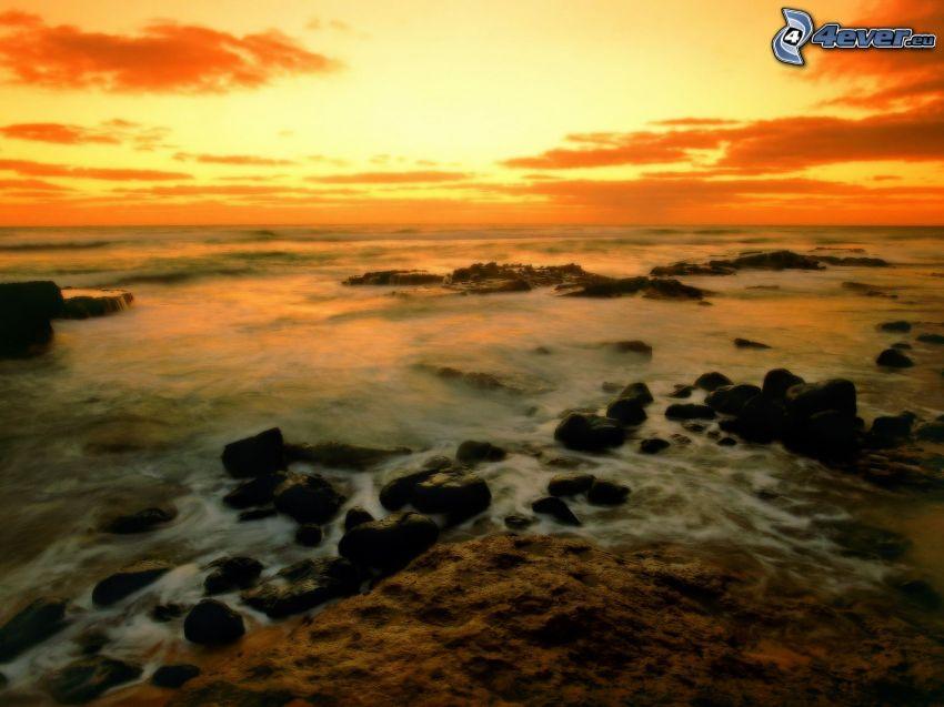 Hawaii, klippor i havet, orange solnedgång, efter solnedgången