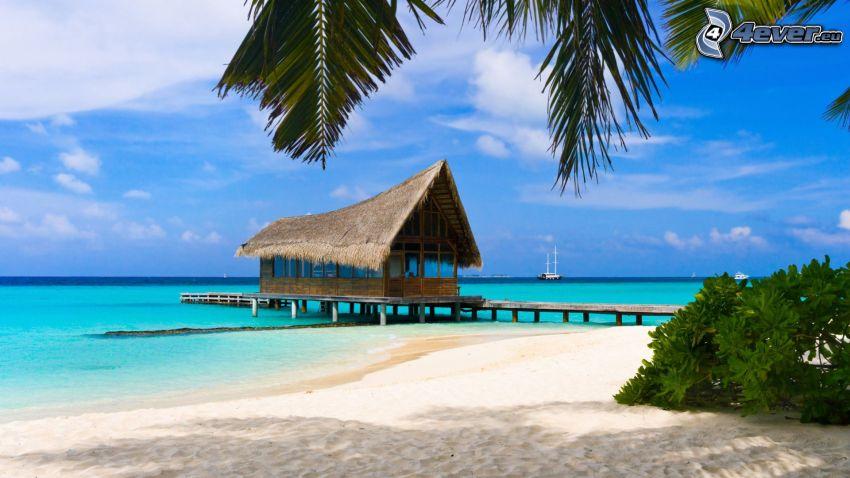 hus på vatten, sandstrand, grunt azurblå hav