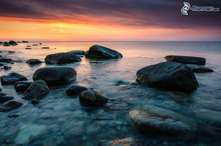 klippor i havet, efter solnedgången, orange himmel