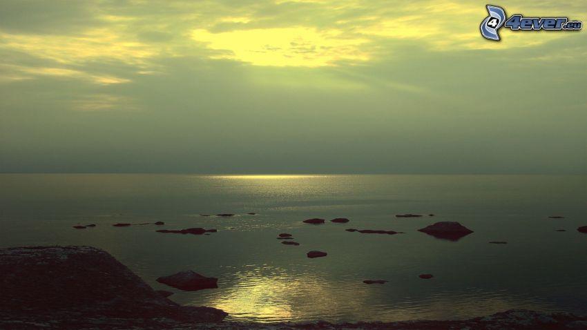 klippor i havet, reflektion av solen